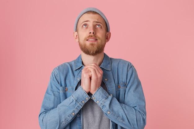 Bebaarde man in denim overhemd en grijze hoed die het gewenste resultaat wil bereiken, handen gevouwen op een zonnevlecht, toont een biddend gebaar, geïsoleerd