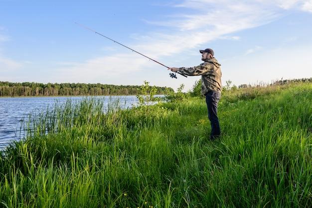 Bebaarde man in een blauwe baseballpet op de rivier gooit een draaiende visserij