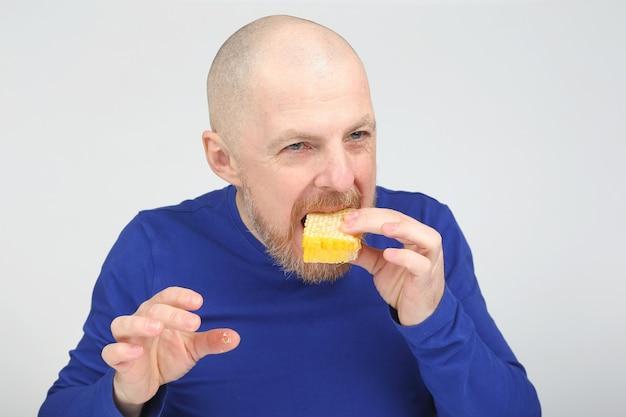 Bebaarde man in een blauwe trui die een honingraat eet