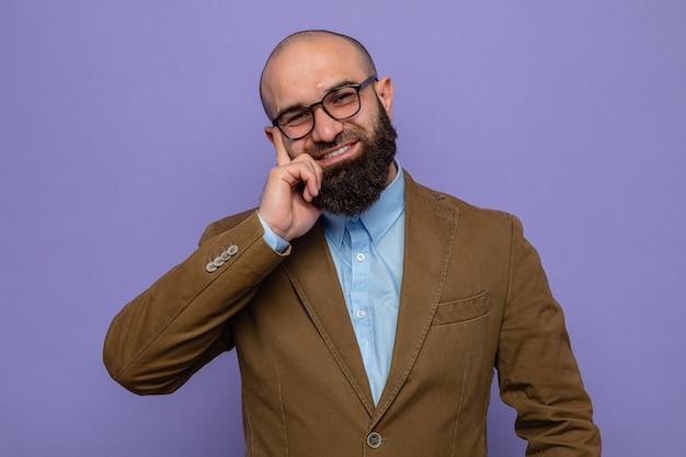 Bebaarde man in een bruin pak met een bril die naar de camera kijkt, blij en vrolijk glimlacht, in het algemeen over een paarse achtergrond