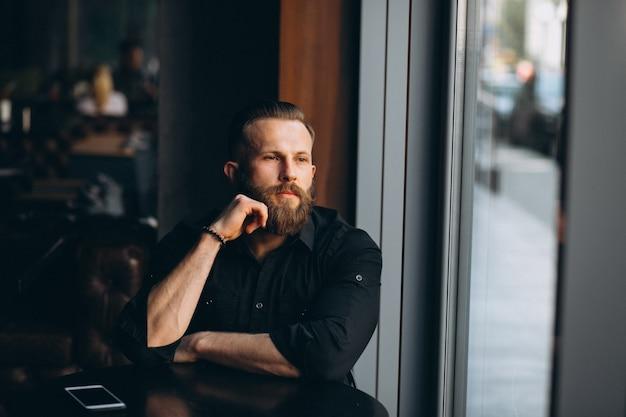 Bebaarde man in een café
