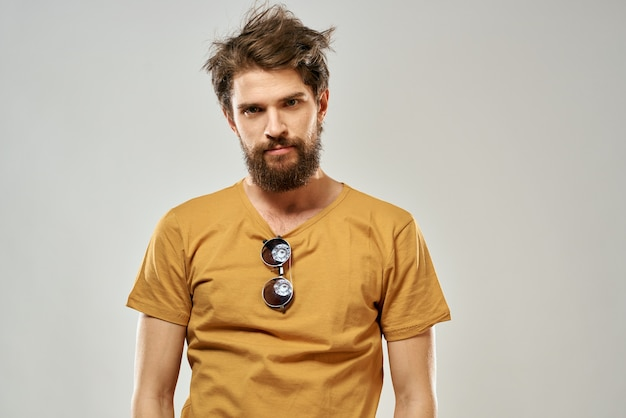 Bebaarde man in een gele t-shirt donkere glazen emoties lichte levensstijl mode.