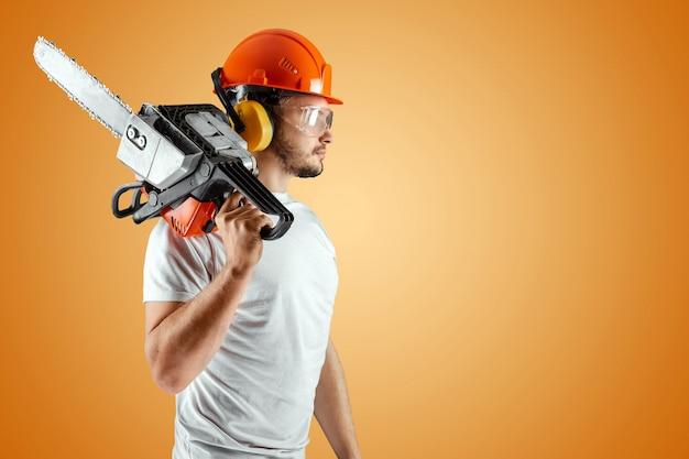 Bebaarde man in een helm heeft een kettingzaag op een oranje achtergrond