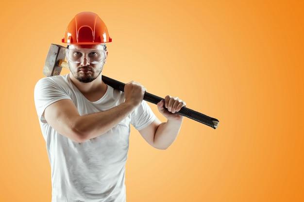Bebaarde man in een helm heeft een voorhamer op een oranje achtergrond