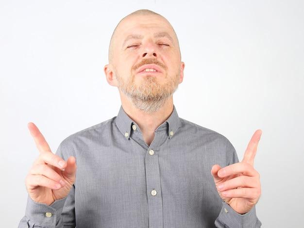 Bebaarde man in een overhemd staat met zijn ogen dicht en zijn hand omhoog