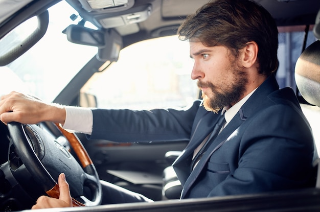 Bebaarde man in een pak in een auto een reis naar het werk rijk