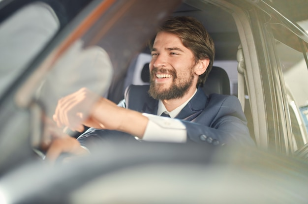 Bebaarde man in een pak in een auto een reis naar het werk succes service rijk