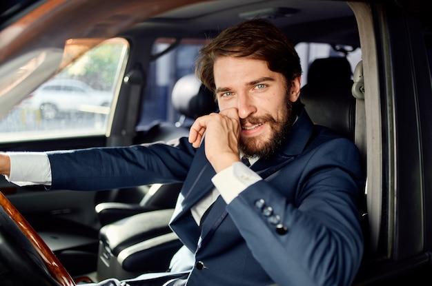 Bebaarde man in een pak in een auto een reis om zelfvertrouwen te werken. hoge kwaliteit foto