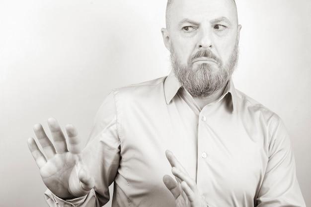 Bebaarde man in een shirt met een ontevreden gezichtsuitdrukking en negatieve emoties