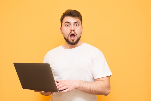 Bebaarde man in een wit t-shirt met een laptop in zijn handen is geïsoleerd op een geel
