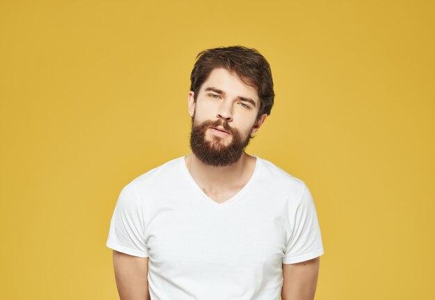 Bebaarde man in een witte t-shirt geïrriteerde gezichtsuitdrukking levensstijl