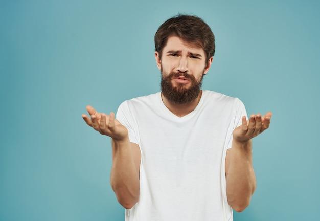 Bebaarde man in een witte t-shirt handgebaren woede studio