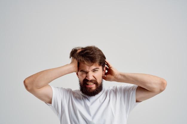 Bebaarde man in een witte t-shirt hoofdpijn migraine problemen geïsoleerde achtergrond