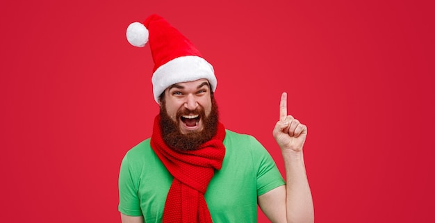 Bebaarde man in elfkleren die tijdens kerstmis omhoog wijst