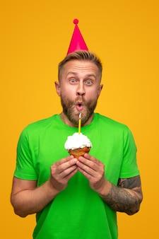 Bebaarde man in feestmuts camera kijken en kaars blazen op muffin terwijl het vieren van verjaardag geïsoleerd op geel