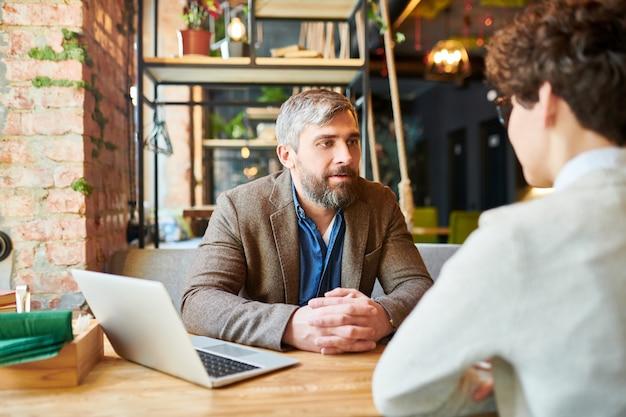 Bebaarde man in formalwear hebben praten met collega of een van klanten tijdens bijeenkomst in café