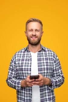Bebaarde man in geruit overhemd glimlachend en camera browsen smartphone kijken