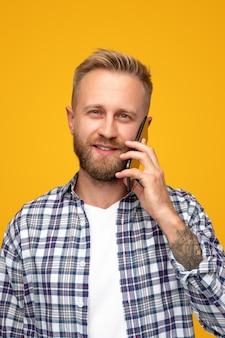Bebaarde man in geruite overhemd met oproep op smartphone op helder geel