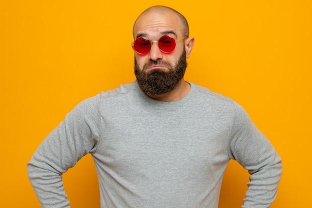 Bebaarde man in grijs sweatshirt met een rode bril die naar de camera kijkt met een sceptische uitdrukking over een oranje achtergrond