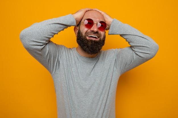 Bebaarde man in grijs sweatshirt met een rode bril kijkt blij en opgewonden op en houdt handen op zijn hoofd