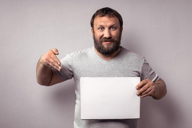 Bebaarde man in grijze t-shirt met lege witte posterholding en wijzend met de hand op witte kaart