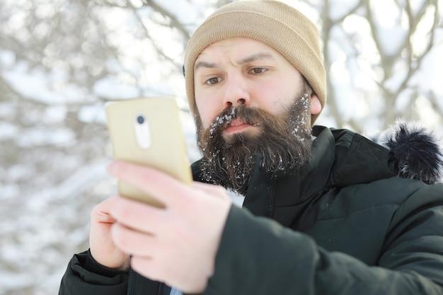 Bebaarde man in het bos van de winter. aantrekkelijke gelukkige jonge man met baard lopen in het park.