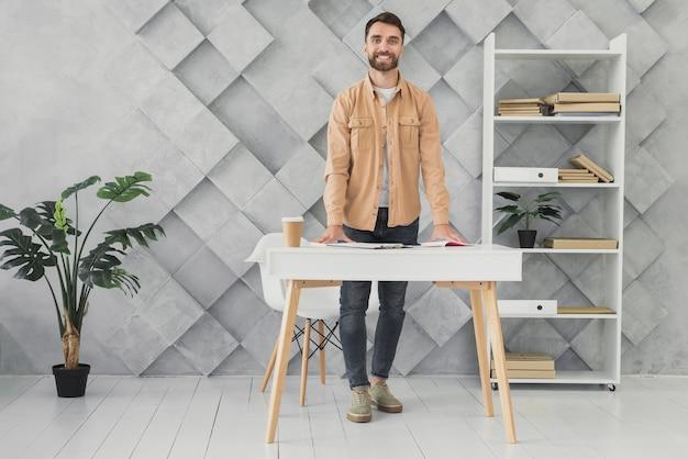 Bebaarde man in het kantoor afstandsschot