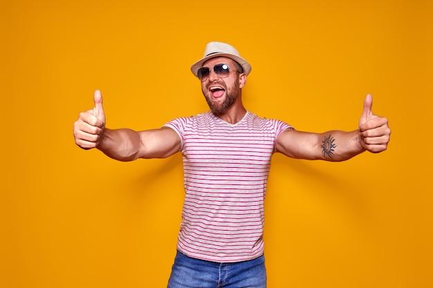 Bebaarde man in hoed en zonnebril duimen opdagen