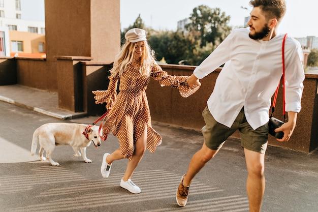 Bebaarde man in kaki korte broek houdt blond meisje met de hand vast en rent. paar genieten van zomerwandeling met hond.