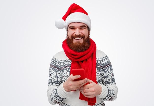 Bebaarde man in kerstmuts glimlachen tijdens het browsen smartphone