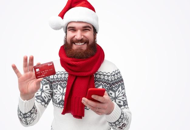 Bebaarde man in kerstmuts glimlachend en creditcard demonstreren