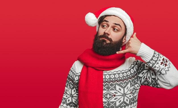 Bebaarde man in kerstmuts met denkbeeldige telefoon