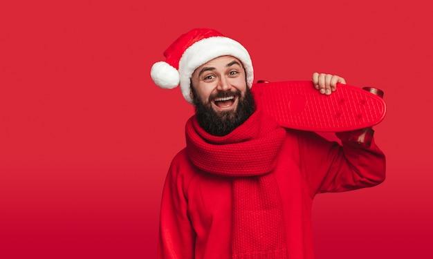 Bebaarde man in kerstmuts met skateboard