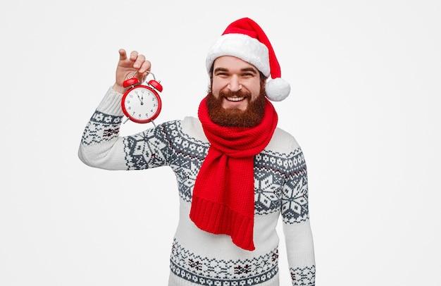 Bebaarde man in kerstmuts wachten op het aftellen van het nieuwe jaar