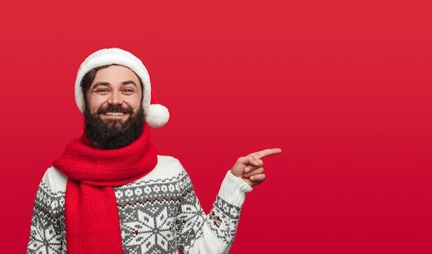 Bebaarde man in kerstmuts wijst opzij
