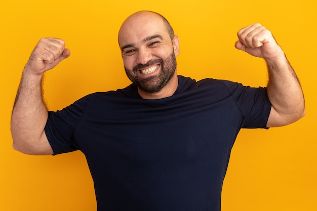 Bebaarde man in marine t-shirt blij en opgewonden vuisten opheffen als een winnaar die over oranje muur staat