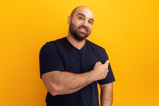 Bebaarde man in marine t-shirt glimlachend zelfverzekerd wijzend terug staande over oranje muur