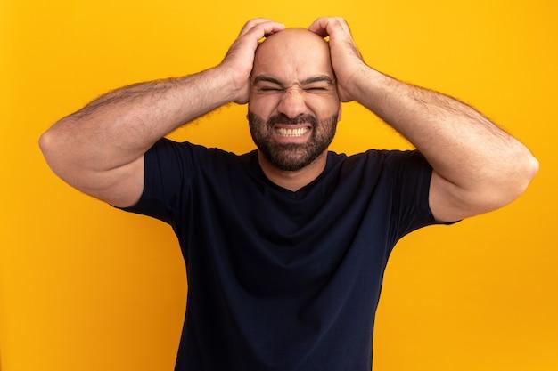 Bebaarde man in marine t-shirt kijkt verward en gefrustreerd met handen op zijn hoofd staande over oranje muur