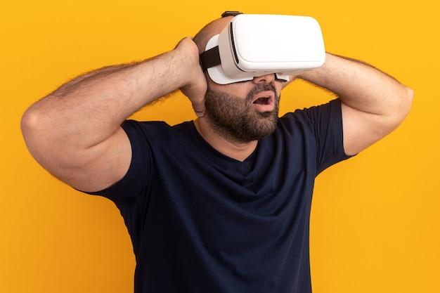 Bebaarde man in marine t-shirt met bril van virtual reality kijkt verbaasd en verrast staande over oranje muur