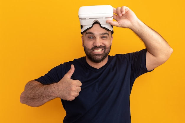 Bebaarde man in marine t-shirt met bril van virtuele realiteit blij en positief glimlachend duimen opdagen staande over oranje muur