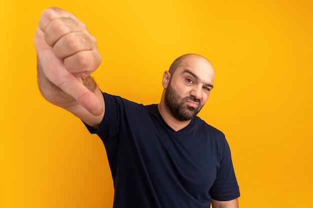 Bebaarde man in marine t-shirt ontevreden met duimen naar beneden staande over oranje muur