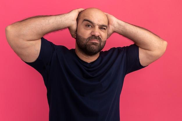 Bebaarde man in marine t-shirt ontevreden met handen achter zijn hoofd staande over roze muur