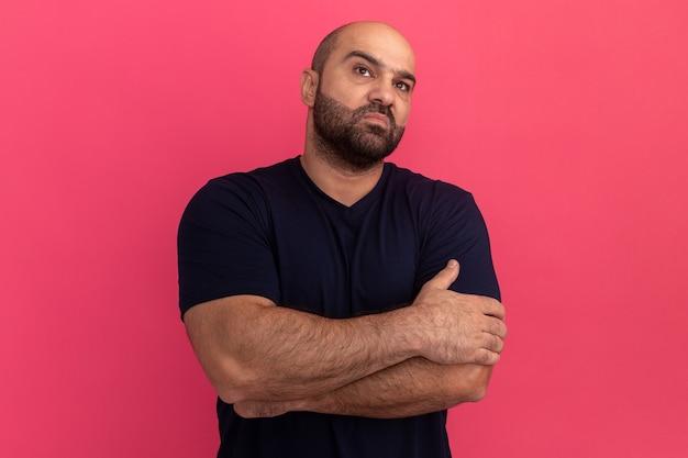 Bebaarde man in marine t-shirt opzij kijken ontevreden met gekruiste armen staande over roze muur
