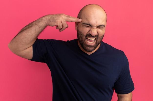 Bebaarde man in marine t-shirt schreeuwen met geïrriteerde uitdrukking wijzend met wijsvinger naar zijn tempel die over roze muur staat