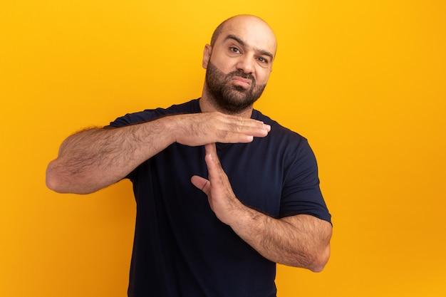 Bebaarde man in marine t-shirt waardoor time-out gebaar wordt gediplomeerd staande over oranje muur