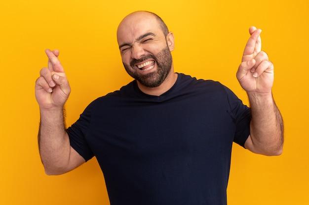 Bebaarde man in marine t-shirt wenselijke wens maken met hoop expressie vingers kruisen met gesloten ogen staande over oranje muur