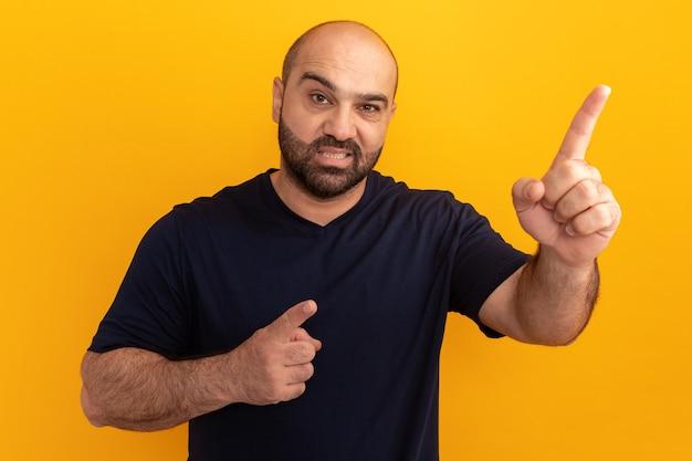 Bebaarde man in marineblauw t-shirt kijkt verward en ontevreden en wijst met wijsvingers naar iets dat over de oranje muur staat