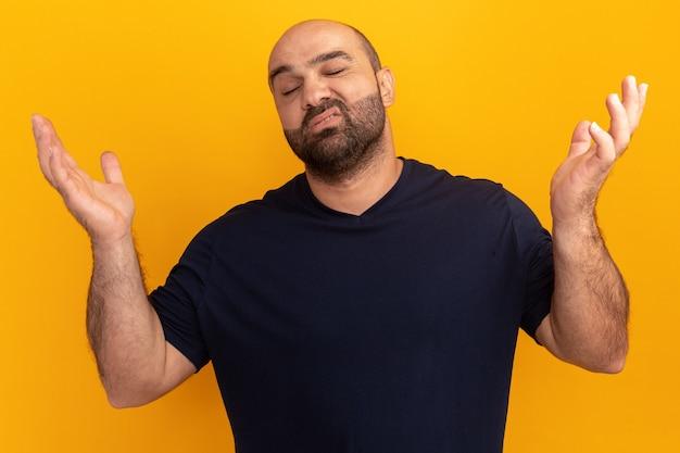 Bebaarde man in marineblauw t-shirt kijkt verward en onzeker met opgeheven armen boven de oranje muur