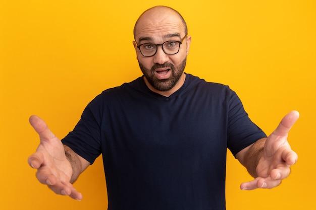 Bebaarde man in marineblauw t-shirt met bril, verward en erg angstig met uitgestrekte armen als vragend staande over oranje muur