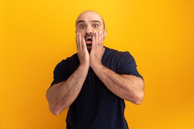 Bebaarde man in marineblauw t-shirt verbaasd en bezorgd met handen op zijn gezicht staande over oranje muur